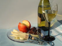 Summer evening with glass of white wine. Glass of white wine, partial of green wine bottle, platter with cheese, peach and chocolate and corkscrew with cork in a Stock Images