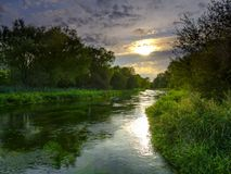 Summer evening golden light on the River Itchen - full of Water Crowfoot (Ranunculus aquatilis) and a well known chalk stream fly. Fishing river - near Martyr royalty free stock images