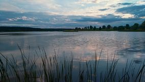 Summer evening at lake with dramatic sky and reflection in water and grass on foreground.  stock footage