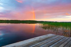 Summer evening on a lake with a rainbow. Stock Image