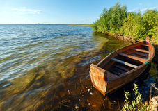 Summer evening lake view with wooden boat. Royalty Free Stock Photo