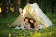 Summer evening in love couple  lay inside cute tent at the park. Stock Images