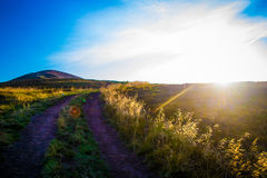 Summer evening mountain landscape. Road through the hill to the top. mountain ridge is seen in the distance. Evening sun colors dry grass in gold Stock Photography