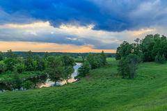 Summer evening, the river flows through a field. A forest in the distance, the sky dark blue clouds Stock Images