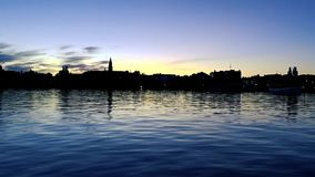 Summer evening at Savonlinna Finland. View over the harbor basin with shallow waves and the silhouette of the cathedral peninsula in the background stock video
