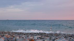 Summer evening at sea coast. Small waves surf on gray pebbles. stock video footage