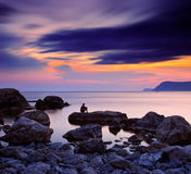 A man sitting on a rock by the sea Royalty Free Stock Images