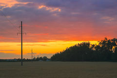 Summer evening sky - warm background. High voltage power line on the evening stock image