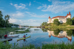 Summer evening in Sweden. Lidkoping, Sweden - July 23, 2016: Tourists kayaking on a summer evening by Lake Vanern and Lacko Castle. Lacko castle dating back to Stock Photo