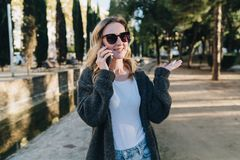 Summer evening. A young attractive woman in sunglasses stands in the park and talks happily on her cell phone Stock Image