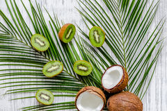 Summer exotic fruits. Kiwi, coconut and palm branch on wooden background top view Stock Images