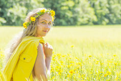 Summer fairy. Attractive young woman with flower wreath on her head with yellow flowers field in background Royalty Free Stock Image