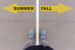 Summer and fall text arrows on asphalt ground, feet and shoes on Stock Photo