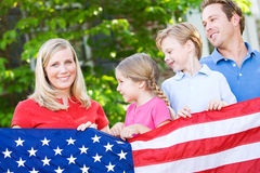 Summer: Family with American Flag. Series with a Caucasian family outdoors, on a summer day - mother, father, son, daughter.  Overall a July 4th holiday theme Royalty Free Stock Photography
