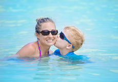 Summer family fun at the swimming pool. Mother and son playing together in an outdoor swimming pool. Boy kissing his smiling mom in the water. Fun time together Royalty Free Stock Photos