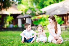 Summer family portrait. Summer portrait of mother and kids sitting on grass Royalty Free Stock Photo