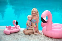 Summer family vacation. Fashion look blond girls portrait. Beaut. Iful Mother holding her little daughter, wears in swim wear posing with Inflatable Flamingo royalty free stock photography