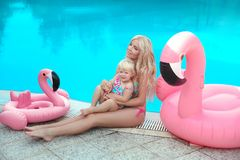 Summer family vacation. Fashion look blond girls portrait. Beaut. Iful Mother holding her little daughter, wears in swim wear posing with Inflatable Flamingo stock photography