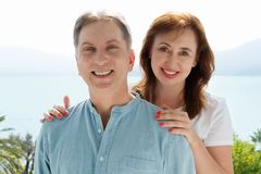 Summer family vacation. Happy middle aged couple having fun on travel holidays weekend. Sea and beach background. Copy space.  royalty free stock photo