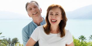 Summer family vacation. Happy middle aged couple having fun on travel holidays weekend. Sea and beach background. Copy space.  royalty free stock images