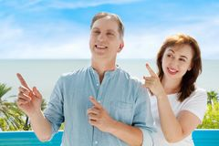 Summer family vacation. Happy middle aged couple having fun on travel holidays weekend. Sea and beach background. Copy space. Selective focus royalty free stock photography