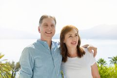Summer family vacation. Happy middle aged couple having fun on travel holidays weekend. Sea and beach background. Copy space.  stock photo