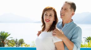 Summer family vacation. Happy middle aged couple having fun on travel holidays weekend. Sea and beach background. Copy space. Selective focus royalty free stock images