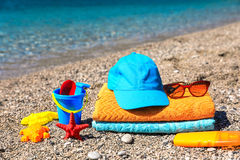 Summer family vacation by the sea concept. Beach towels, cap, sunglasses, children& x27;s toys, seashells and sunscreen on the beach on the sea background Royalty Free Stock Photo