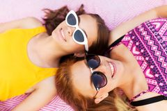 Teenage girls in sunglasses on picnic blanket Royalty Free Stock Photo