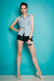 Summer fashion girl in jeans shirt shorts and high heels. Royalty Free Stock Image