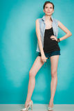 Summer fashion girl in jeans shirt shorts and high heels. Royalty Free Stock Photo