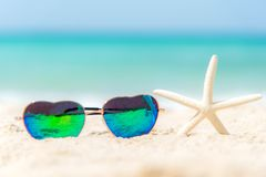 Summer Fashion heat shape sunglasses on sea beach under clear blue sky. Summer holiday relax background, copy space Royalty Free Stock Images