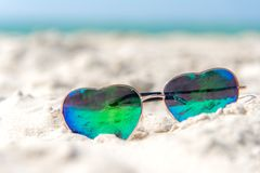 Summer Fashion heat shape sunglasses on sea beach under clear blue sky. Summer holiday relax. Background with copy space Royalty Free Stock Image