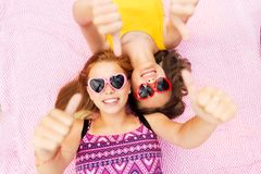 Teenage girls in sunglasses showing thumbs up Royalty Free Stock Photo