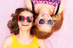 Teenage girls in sunglasses on picnic blanket Stock Photos