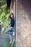 Summer, fashion and people concept - young woman posing outdoor. Over brick wall,street fashion Royalty Free Stock Image