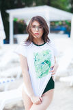 Summer fashion portrait of stunning woman with tanned fit body, wearing white t-shirt with green print, Swimsuit. And stylish green sunglasses, posing at beach royalty free stock image