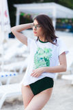 Summer fashion portrait of stunning woman with tanned fit body, wearing white t-shirt with green print, Swimsuit. And stylish green sunglasses, posing at beach royalty free stock images