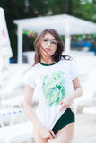Summer fashion portrait of stunning woman with tanned fit body, wearing white t-shirt with green print, Swimsuit. And stylish green sunglasses, posing at beach stock image