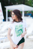 Summer fashion portrait of stunning woman with tanned fit body, wearing white t-shirt with green print, Swimsuit. And stylish green sunglasses, posing at beach royalty free stock photo