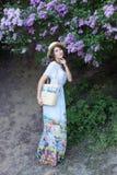 Summer fashion portrait of stunning woman walking in the blooming lilac garden. Wearing long vintage dress. Romantic mood. Secret stock photo
