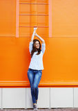 Summer fashion, pretty woman posing in the urban style. Against bright colorful wall Stock Photography