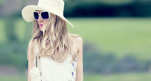 Summer fashion romantic lady in the park on a walk. Fashion hat and sunglasses Stock Photo