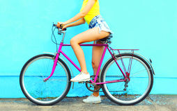 Summer fashion woman with bicycle. On a colorful blue background in profile view Stock Images