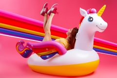 Pink and joyful mood. Summer fashionable girl, pink and joyful mood. Beautiful slim woman in a summer clothes, having fun and enjoying life on a white inflatable royalty free stock photo