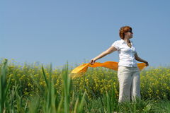 Summer feeling. Concept of a young woman in a grass field playing with her scarf in the wind Royalty Free Stock Photos