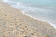 Soft waves of the sea and a lot of shells. Summer feeling . Calm sea, soft waves and a lot of shells stock photography