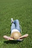 Summer feelings. Young woman lies in a deckchair in the sun Stock Photos