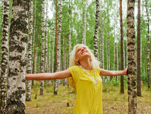 Summer feelings. Happy young woman standing between birch trees Stock Images