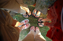 Summer Feet. A group of teen girlfriends stand in a huddle showing their painted toe nails and summer sandals stock photos